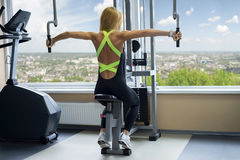 Woman shakes her shoulders in gym Stock Photography