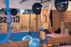 Woman shakes her shoulders in gym Royalty Free Stock Photography