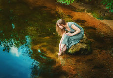 Woman sitting on the rock in a pond Stock Photos