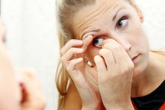 Woman take out contact lens of her eye Stock Photo