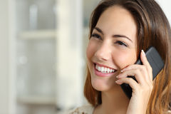 Woman talking on the mobile phone at home Royalty Free Stock Photos