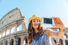 Woman tourist taking selfie at Colosseum in Rome in summer Stock Photo