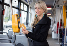 Woman using electronic ticket punching machine in public transport Royalty Free Stock Image