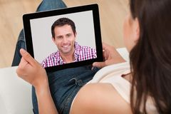 Woman video chatting with man Royalty Free Stock Image