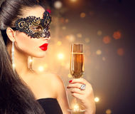 Woman wearing carnival mask with glass of champagne Royalty Free Stock Images