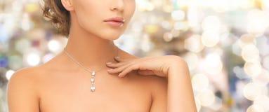 Woman wearing shiny diamond pendant Stock Image