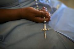 Women and religion, catholic sister praying in church, holding c Stock Image