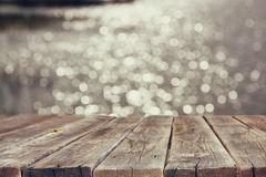 Wood board table in front of summer landscape of sparkling lake water. background is blurred Stock Photography