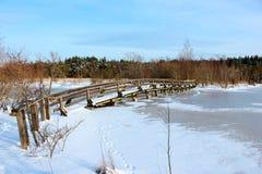 A wooden bridge over a frozen river Stock Image