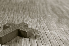 Wooden Christian cross on a rustic wooden surface, sepia toning Royalty Free Stock Image