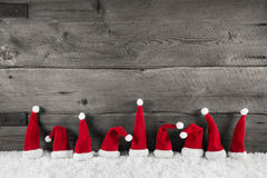 Wooden christmas background with red santa hats for a festive fr Stock Images