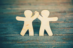 Wooden men holding hands Stock Photography