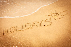 The word holidays written in the sand on a beach Royalty Free Stock Photography
