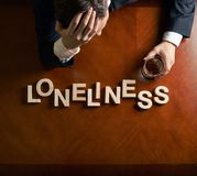 Word Loneliness and devastated man composition Stock Photos