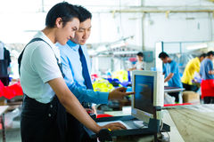Foreman in a factory explains something Royalty Free Stock Image