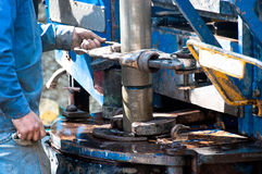 Worker screwing on a drill casing Royalty Free Stock Photography
