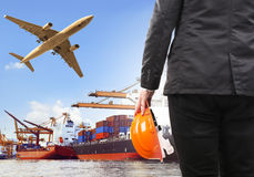 Working man and commercial ship on port and air cargo plane flyi Stock Photos