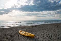 Yellow canoe on a sandy beach near to the sea Stock Images