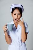 Young Asian nurse yawn with a cup of coffee Royalty Free Stock Photos