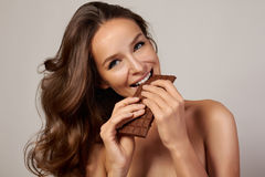 Young beautiful girl with dark curly hair, bare shoulders and neck, holding a chocolate bar to enjoy the taste and a Royalty Free Stock Photo
