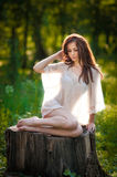 Young beautiful red hair woman wearing a transparent white blouse posing on a stump in a green forest. Fashionable sexy girl Royalty Free Stock Images