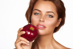 Young beautiful sexy girl with dark curly hair, bare shoulders and neck, holding big red apple to enjoy the taste and are dieting, Stock Photos