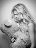 Young blonde sensual woman looking at a huge teddy bear. Beautiful girl holding an over sized toy. Attractive blonde in cosy scene Stock Image