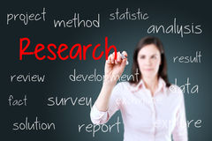 Young business woman writing research concept. Blue background. Royalty Free Stock Photography