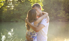 Young couple embracing on a bank of river Royalty Free Stock Images