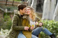 Young couple in love kissing tenderly on street celebrating Valentines day or anniversary cheering in Champagne Royalty Free Stock Photography