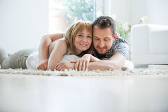 Young couple lying in living room on carpet, embracing Stock Photography