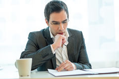 Young executive thoughtfuly and attentively reading a job applic Stock Photography