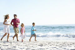 Young Family Running Along Sandy Beach On Holiday Royalty Free Stock Photos