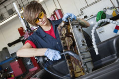 Young female mechanic working with welding torch on vehicle machinery part in auto repair shop Stock Photo