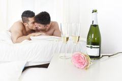 Young gay men couple kissing on bed with rose after champagne toast celebrating valentines day in homosexual love concept Royalty Free Stock Photography