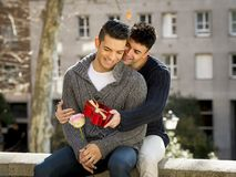 Young  gay men couple with rose and box present celebrating valentines day in love Stock Photo