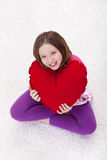 Young girl with large red heart pillow Stock Photos