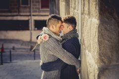 Young happy attractive gay men couple holding rose hugging and kissing outdoors Valentines free homosexual love Royalty Free Stock Photos