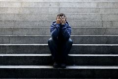 Young homeless man lost job sitting in depression on ground street concrete stairs Royalty Free Stock Photo