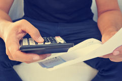 Young man checking a bill, a budget or a payroll, filtered Royalty Free Stock Photos