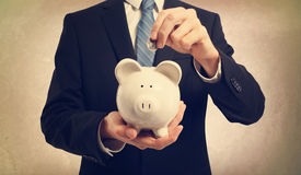 Young man depositing money in piggy bank Royalty Free Stock Photos
