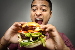 Young Man have a great desire to eat a burger Royalty Free Stock Photography
