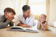 Young man with two kids reading a story book Stock Images
