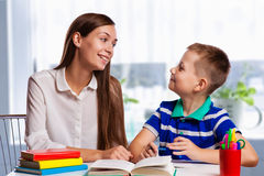 Young mother sitting at a table at home helping her small son with his homework from school as he writes notes in a notebook Stock Images