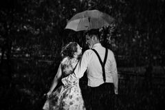 Young romantic couple in love flirting in rain. Black and white Stock Photo