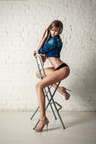 Young sexy beautiful blonde woman posing on chair Royalty Free Stock Image