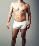 Young sexy man posing in white pants. Royalty Free Stock Photos
