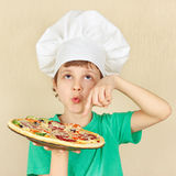 Young smiling kid in chefs hat with cooked appetizing pizza Royalty Free Stock Photo
