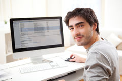 Young smiling man in front of computer Stock Images