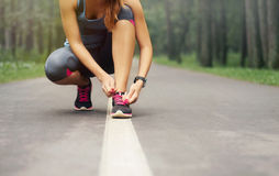 Young sporty woman preparing to run in early foggy morning in th Royalty Free Stock Photos